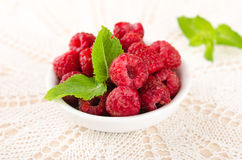 Ripe sweet raspberries in bowl on table. With mint leaves Royalty Free Stock Photo