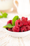 Ripe sweet raspberries in bowl on table. With mint leaves Royalty Free Stock Photos