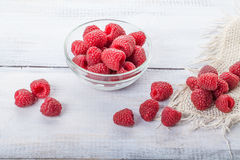 Ripe sweet raspberries in bowl on white wooden table Royalty Free Stock Photos