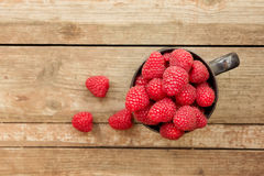 Ripe sweet raspberries in bowl on wooden tabl. E. Close up, top view, high resolution product Royalty Free Stock Image