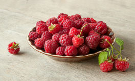 Ripe sweet raspberries in bowl on wooden table. Close-up of Ripe sweet raspberries in bowl on wooden table Stock Photography