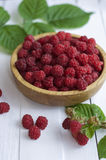 Ripe sweet raspberries in bowl on wooden table. Close up, top vi. Fresh raspberries in a wooden bowl with green leaves from a bush on a white table Royalty Free Stock Photography