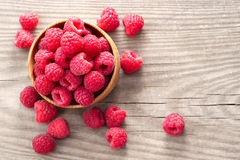 Ripe sweet raspberries in bowl on wooden table. Close up, top view, high resolution product Royalty Free Stock Photos