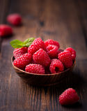Ripe sweet raspberries in bowl on wooden table. Close up, top view, high resolution product Royalty Free Stock Photography