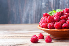 Ripe sweet raspberries in bowl on wooden table, closeup. Selective focus Royalty Free Stock Image