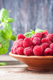 Ripe sweet raspberries in bowl on wooden table, closeup. Selective focus Royalty Free Stock Images
