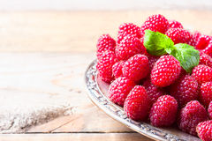 Ripe sweet raspberries in bowl on wooden table, closeup. Selective focus Royalty Free Stock Photography
