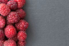 Ripe sweet raspberries on dark background. Close up, top view, with copy space. Ripe sweet raspberries on dark background. Close up, top view, with copy space Stock Photos