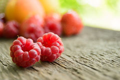 Ripe Sweet Raspberries and Fruits on the Wooden Table. Ripe Sweet Raspberries on the Wooden Table Against the Heap of Summer Fruits and Berries Royalty Free Stock Image