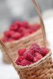 Ripe sweet raspberries in small wicker basket. Close up Stock Image