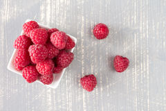 Ripe sweet raspberries-top view. Fresh raspberries in white bowl on the grey wooden background Royalty Free Stock Photos