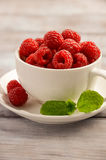 Ripe sweet raspberries in white cup on wooden table. Selective focus, close up, copy space Stock Photos