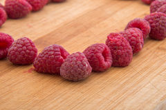 Ripe sweet raspberries on wood table close-up Royalty Free Stock Image
