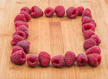 Ripe sweet raspberries on wood table close-up Royalty Free Stock Photography