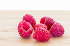 Ripe sweet raspberries on wooden table Stock Photos