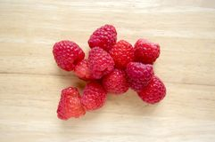 Ripe sweet raspberries on wooden table, isolated. Red fresh raw fruits spilled Royalty Free Stock Image