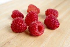 Ripe sweet raspberries on wooden table,. Tasty dark red fruits Stock Images
