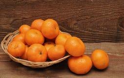 Ripe tangerine fruits in basket Stock Images