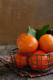 Ripe tangerine fruits in wire basket Stock Image