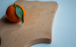 A ripe tangerine with a green leaf on a wooden deck royalty free stock images