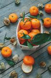 Ripe tangerines and fruits of fezalis with leaves and twigs on an old wooden table. The view from the top royalty free stock photos