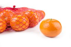 Ripe tangerines in the net bag on a white background.  royalty free stock image