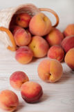 Ripe tasty peaches in a basket on a light wooden background. Royalty Free Stock Image