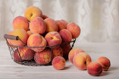 Ripe tasty peaches in a basket on a light wooden background. Stock Photo