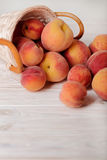 Ripe tasty peaches in a basket on a light wooden background. Stock Image