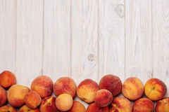 Ripe tasty peaches on a light wooden background. Royalty Free Stock Images