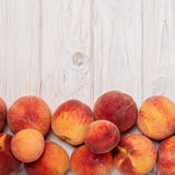 Ripe tasty peaches on a light wooden background. Stock Image