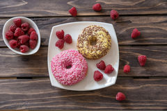 Ripe tasty raspberries and donuts on wooden background.Selective focus. Ripe tasty raspberries and donuts on wooden background Stock Photo