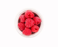 Ripe and tasty raspberries isolated on white background. Raspberries in a white ceramic bowl. Ripe and tasty raspberries isolated on white background. Top view Stock Photos