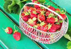 Ripe and tasty strawberries metal a basket in the street on green bench Royalty Free Stock Photos
