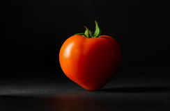 Ripe tomato on a dark background. Ripe and tasty tomatoes in the shape of a heart on a dark background Royalty Free Stock Photography