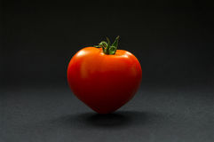 Ripe tomato on a dark background. Ripe and tasty tomatoes in the shape of a heart on a dark background Stock Photo