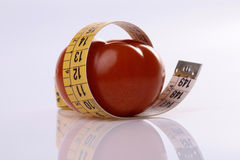 Ripe tomato and measuring tape Stock Images