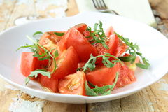 Ripe tomato salad with arugula in a rustic style Royalty Free Stock Photos