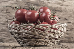 Ripe tomatoes in a basket on wooden table Stock Photography
