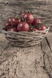 Ripe tomatoes in a basket on wooden table Stock Images