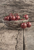 Ripe tomatoes in a basket on wooden table Stock Photo