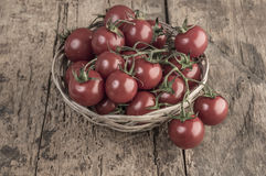 Ripe tomatoes in a basket on wooden table Royalty Free Stock Image
