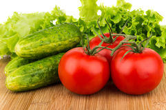 Ripe tomatoes on branch, cucumbers and lettuce on board Stock Images