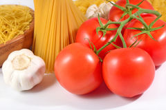 Ripe tomatoes branch, uncooked Italian pasta spaghetti and garli Royalty Free Stock Photo