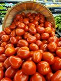 Ripe tomatoes in bushel basket. Close up of ripe tomatoes spilling out of wooden bushel basket in the produce department royalty free stock photos
