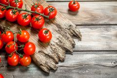 Ripe tomatoes on a cutting Board. On wooden background royalty free stock image