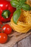 Ripe tomatoes, dried pasta, fresh basil and pepper close up Royalty Free Stock Image