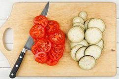 Ripe tomatoes and eggplants cut into slices on cutting board. Ingredients for cooking Stock Photos