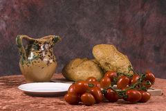 Ripe tomatoes and fresh bread. Ripe tomatoes on vine with fresh bread and earthenware jug, rustic still life scene royalty free stock photo