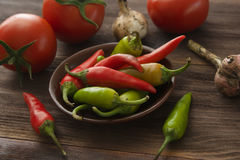 Ripe tomatoes, hot chili peppers, garlic on a wooden table Stock Images